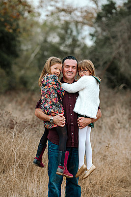 Portrait of happy father carrying daughters while standing on grassy field - p1166m1561036 by Cavan Images