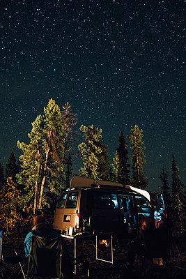 Canada, British Columbia, two men sitting under starry sky at minivan at night - p300m1568029 by Gustafsson