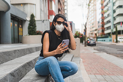 Woman with protective face mask using smart phone while sitting on steps in city - p300m2242333 by MORNINGVIEW AGENCY