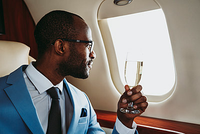 Young businessman with champagne looking through window in private jet - p300m2257020 by OneInchPunch