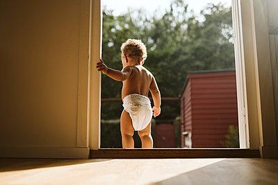 Toddler standing in open door - p312m2162181 by Stina Gränfors