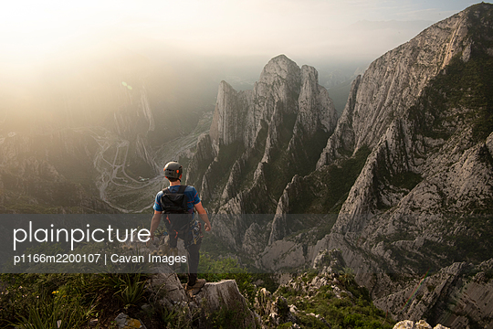 One man standing on a cliff on his way to Nido de Aguiluchos Huasteca - p1166m2200107 by Cavan Images