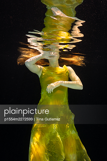 Woman in yellow dress under water - p1554m2272599 by Tina Gutierrez