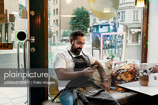 Mid adult man taking break in cafe - p352m2120971 by Folio Images