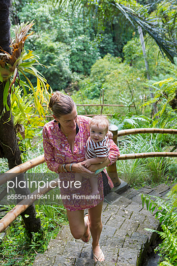 Caucasian mother carrying baby up steps in jungle landscape