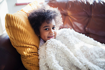 Portrait cute girl relaxing, cuddling on sofa with blanket and pillow - p1023m2016516 by Sam Edwards