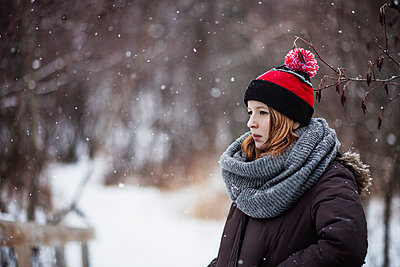 Thoughtful woman standing on field while snowing - p1166m1053892f by Bryant Scannell