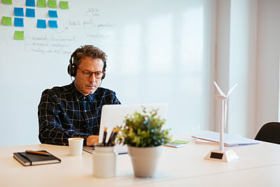 Businessman wearing headphones using laptop at desk in office - p300m1563341 by Bonninstudio