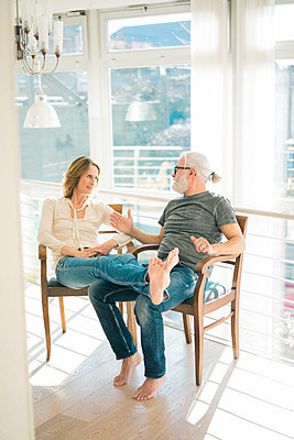 Relaxed mature couple talking on chairs at home - p300m1568302 von Robijn Page