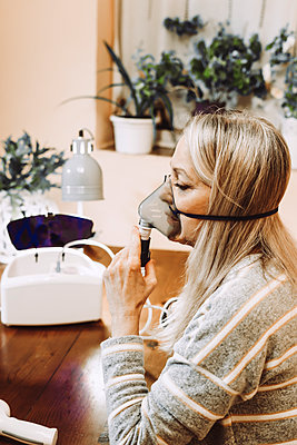 Senior woman with blond hair using nebulizer at home - p300m2240420 by Eloisa Ramos