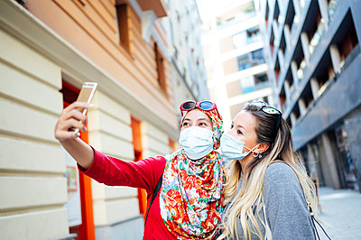 Female friends taking selfie while wearing protective face masks in city during pandemic - p300m2240719 by Jose Luis CARRASCOSA