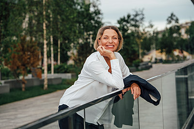 Smiling mature businesswoman with hand on chin leaning on railing - p300m2294222 by Vasily Pindyurin