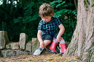Toddler removing shoe beside tree - p429m2164642 by GS Visuals