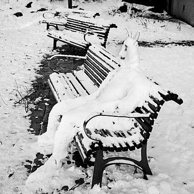 A Snowman sitting on a park bench   - p8476681 by David Lundberg