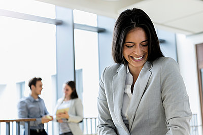Germany, Bavaria, Munich, Smiling young businesswoman standing in corridor - p924m2271294 by suedhang photography