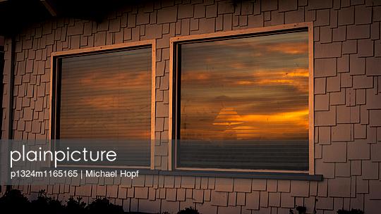 Sonnenuntergang spiegelt sich in Fenster - p1324m1165165 von michaelhopf