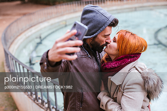 Kissing couple taking selfie with smartphone - p300m2155533 by DREAMSTOCK1982