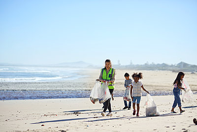 Children volunteers cleaning up beach litter - p1023m2066900 by Trevor Adeline