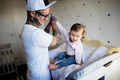 Tätowierter Vater mit Kind im Kinderzimmer - p1212m1108584 von harry + lidy