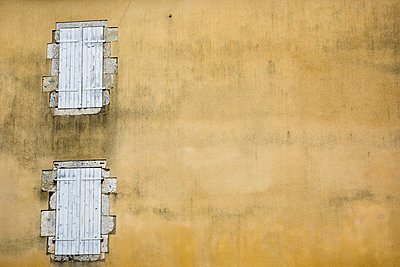 Wall with two wooden shuttered windows. - p1560m2187779 by Alison Morton