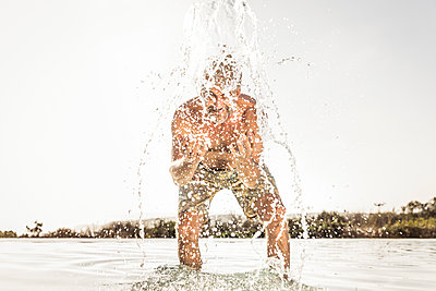 Happy man in swimming pool splashing with water - p300m2167485 by Floco Images