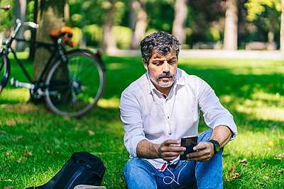Mature man listening music through mobile phone at public park - p300m2225125 by Daniel González