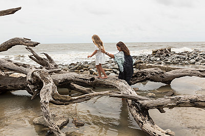 Caucasian mother and daughter walking on driftwood on beach - p555m1504319 by Marc Romanelli