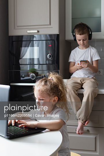 boy listening music and sister using laptop - p1166m2269584 by Cavan Images