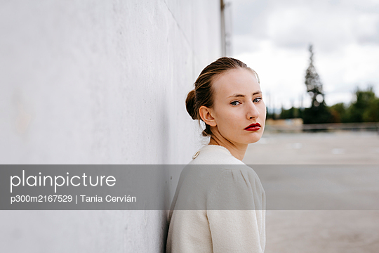 Portrait of serious young woman with red lips leaning against wall - p300m2167529 von Tania Cervián