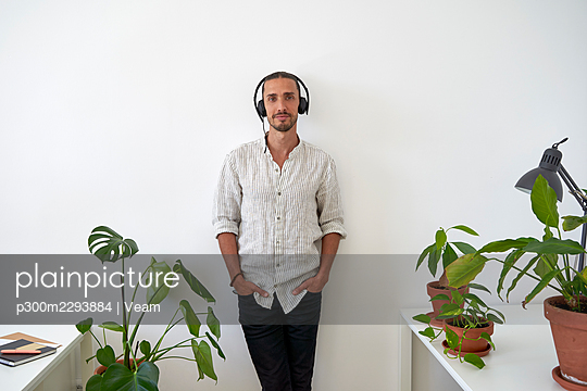 Male customer service representative wearing headphones leaning on wall at office - p300m2293884 by Veam