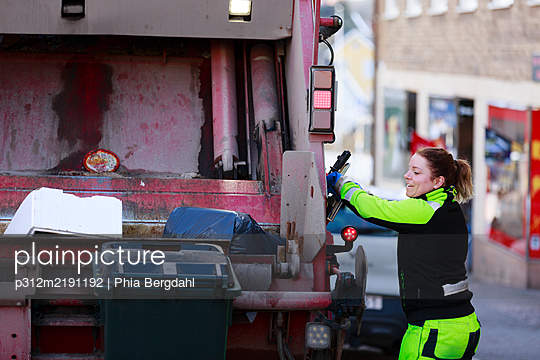 Woman operating garbage truck - p312m2191192 by Phia Bergdahl