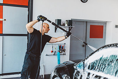 Worker pouring water on car with hose in workshop - p1166m2060366 by Cavan Images