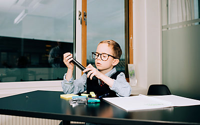 young boy working in an office with his dad doing a presentation - p1166m2153353 by Cavan Images