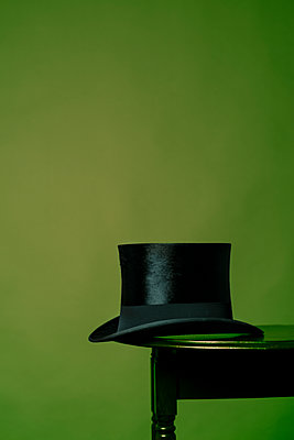 Side profile of a black top hat on the very edge of a small, brown table. - p1433m1589982 by Wolf Kettler
