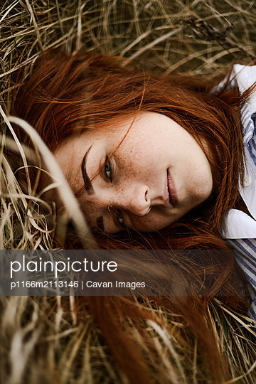 Close-up portrait of teenage girl with red head lying on grassy - p1166m2113146 by Cavan Images