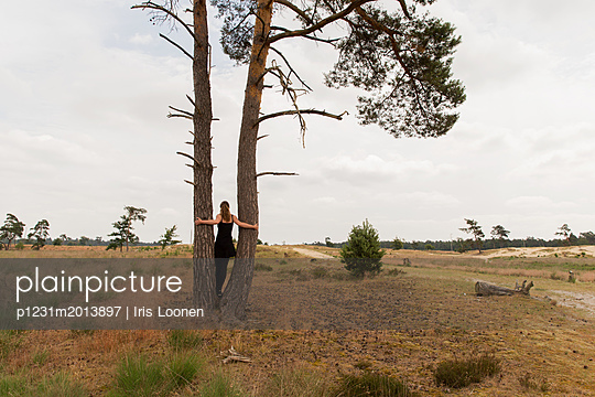 Frau posiert zwischen zwei Bäumen - p1231m2013897 von Iris Loonen
