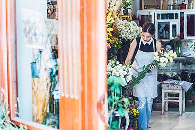 Owner arranging bunch of flowers in shop - p1166m1163886 by Cavan Images