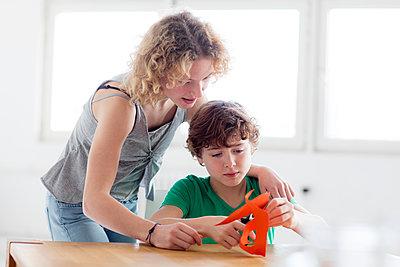 Mädchen hilft Junge beim Basteln - p1212m1094417 von harry + lidy