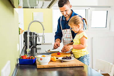 Father and daughter in kitchen preparing fruit cake - p300m1059237f by Uwe Umstätter