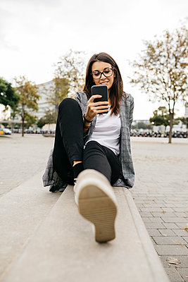 Young businesswoman using smartphone, sitting on bench in the city - p300m2156371 by Josep Rovirosa