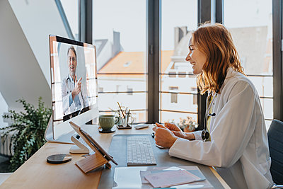 Female doctor talking with coworker over computer while sitting at office - p300m2266886 by Mareen Fischinger