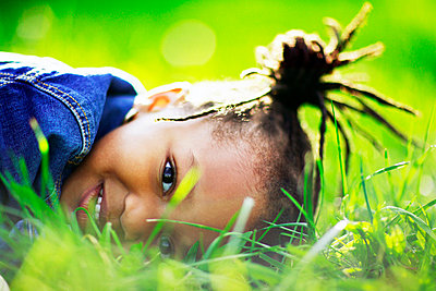 Portrait of young girl laying in grass - p3721766 by James Godman