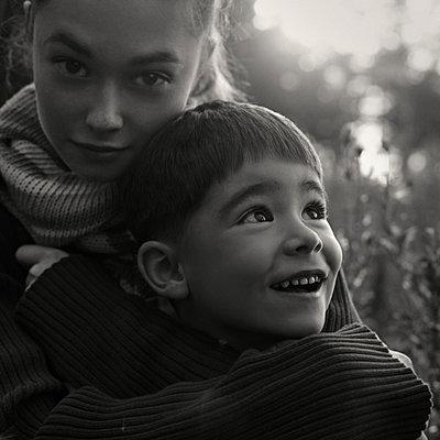 Caucasian women wearing sweater hugging boy - p555m1303323 by Vladimir Serov