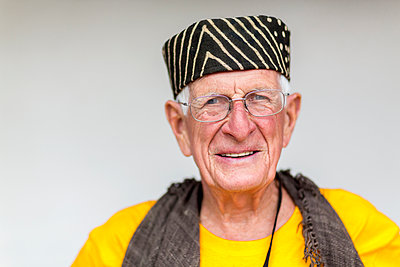Older Caucasian man wearing striped hat - p555m1415683 by Marc Romanelli
