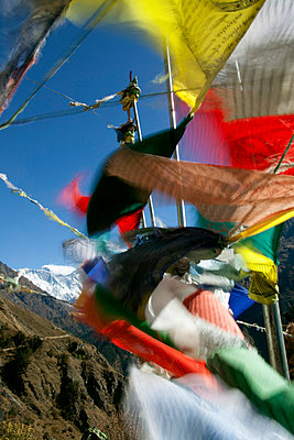 Buddhist prayer flags adorn the trail and frame Mount Everest in the background - p6521227 by Mark Hannaford