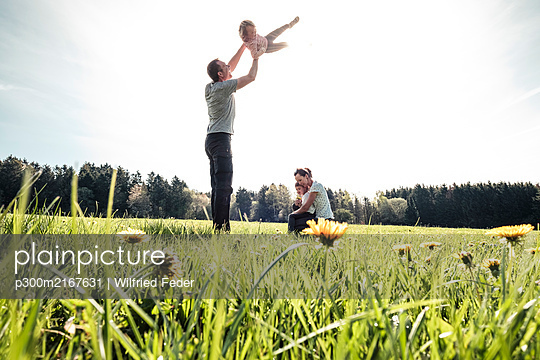 Happy family with two kids on a meadow in spring - p300m2167631 by Wilfried Feder