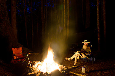 Man relaxing by campfire in forest at night - p1166m1163944 by Cavan Images