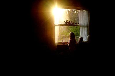 Siblings looking through window while standing in darkroom at home - p1166m1473771 by Cavan Images