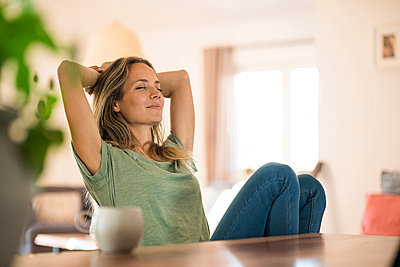 Woman sitting at dining table at home relaxing - p300m2104410 by Steve Brookland