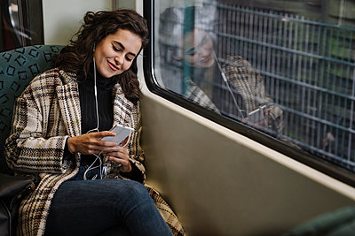 Young woman with earphones using smartphone on a subway - p300m2143448 von Hernandez and Sorokina